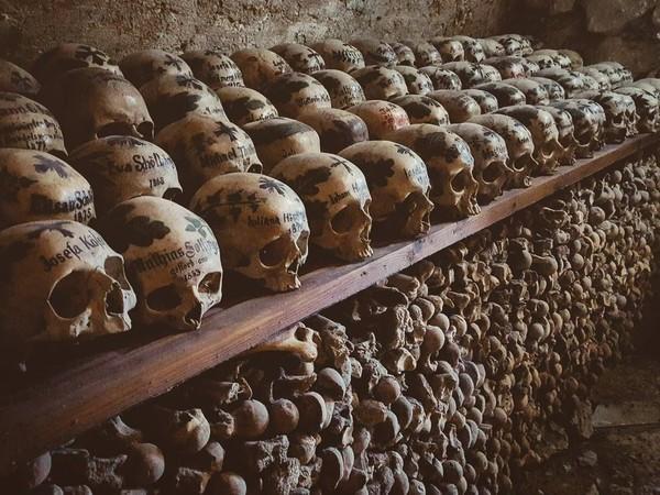 Charnel House dibuat seperti rak yang bersusun. Tulang-tulang badan di bawah rak. Sedangkan tengkoraknya di rak bagian atas, diberi lilin dan salib sebagai tanda penghormatan. (mariasvarela/Instagram)