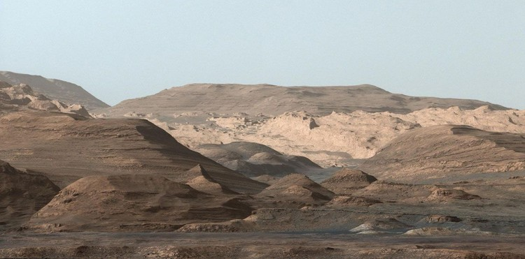 This composite image looking toward the higher regions of Mount Sharp was taken on September 9, 2015, by NASAs Curiosity rover. In the foreground -- about 2 miles (3 kilometers) from the rover -- is a long ridge teeming with hematite, an iron oxide. Just beyond is an undulating plain rich in clay minerals. And just beyond that are a multitude of rounded buttes, all high in sulfate minerals. The changing mineralogy in these layers of Mount Sharp suggests a changing environment in early Mars, though all involve exposure to water billions of years ago. The Curiosity team hopes to be able to explore these diverse areas in the months and years ahead. Further back in the image are striking, light-toned cliffs in rock that may have formed in drier times and now is heavily eroded by winds.  The colors are adjusted so that rocks look approximately as they would if they were on Earth, to help geologists interpret the rocks. This