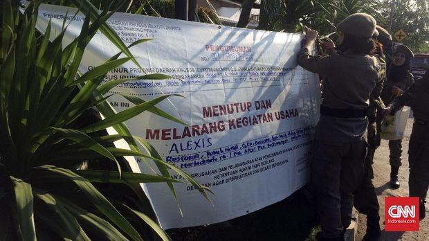 Petugas Satpol PP memasang spanduk pengumuman penutupan Hotel Alexis, Kamis (29/3).