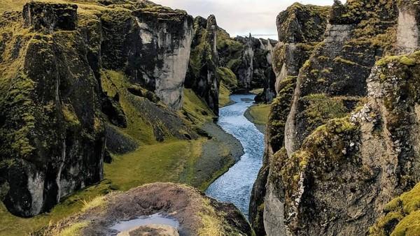 Pemandangan hijau yang membentang di atas tebing berpadu dengan bebatuan tebing yang menjulang tinggi. Di tengah-tengah mengalir air sungai yang sangat jernih. Lukisan Tuhan yang sangat sempurna! (andrewleighow/Instagram)