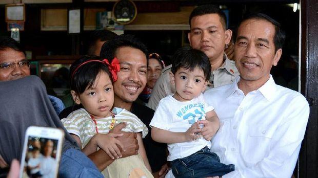 Presiden Jokowi dan cucunya, Jan Ethes, berswafoto bersama warga, di kedai soto Gading, Solo, Jumat (30/3).