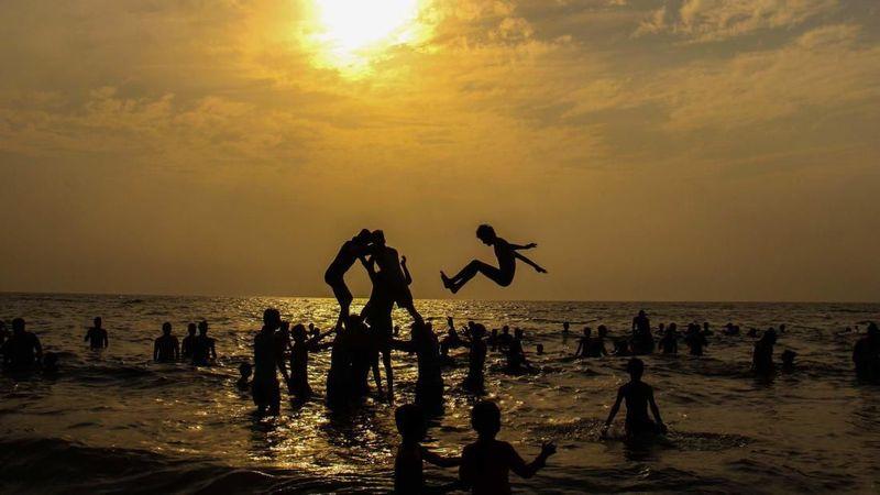 Foto: Sekelompok wisatawan membentuk piramida manusia saat matahari terbenam di Pantai Juhu Mumbai, India pada 25 Maret. Tercatat suhu terpanas di salah satu hari di bulan Maret, yakni 41 derajat celcius (Pramod Thakur/CNN Travel)