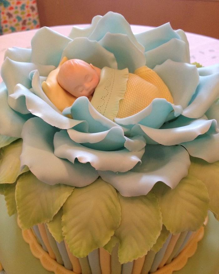 Tidak seperti kue, tapi lebih mirip seperti boneka kan? Fondant berwarna biru muda, hijau dan kuning ini dibentuk seperti bunga mawar yang sedang mekar dan seorang bayi yang sedang tertelap. Foto: Instagram @bakemeacakeorlando