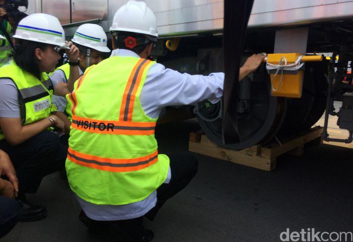 Menhub Budi Karya Sumadi didampingi Direktur Kontruksi PT MRT Jakarta Silvia Halim mengecek bagian bawah gerbong sambil jongkok.