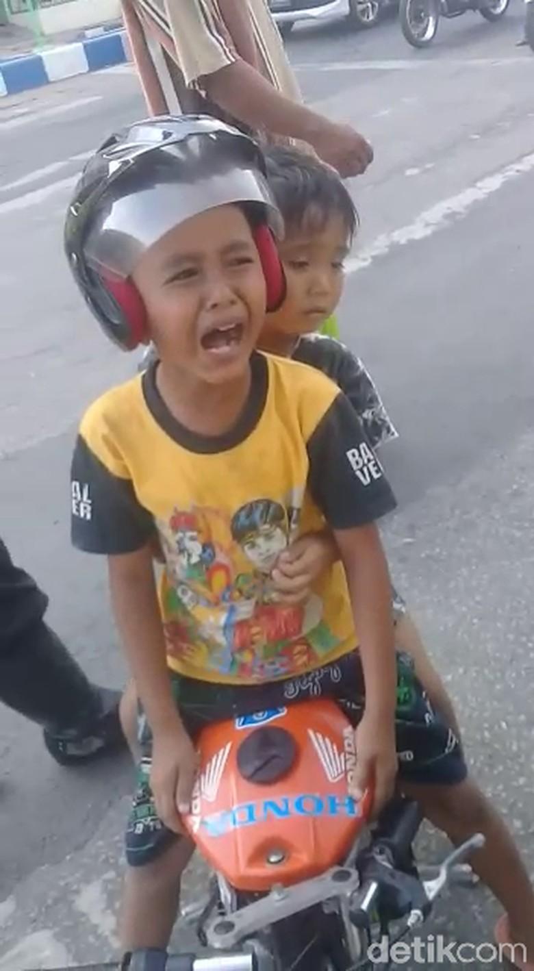 Bocah 5 tahun ini menangis karena mengira motor mininya hendak diambil polisi (Foto: Istimewa)