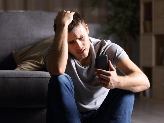 Single sad man checking mobile phone sitting on the floor in the living room at home with a dark background