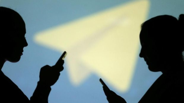 REFILE - CLARIFYING CAPTION Silhouettes of mobile users are seen next to a screen projection of Telegram logo in this picture illustration taken March 28, 2018.  REUTERS/Dado Ruvic/Illustration