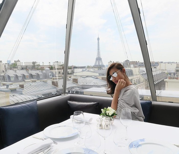 Tetap keren! Pat berpose di sebuah restoran dengan pemandangan Menara Eiffel di belakangnya. Meski makanan belum datang, yang penting sudah pose ya! Foto: Instagram patriciagouw
