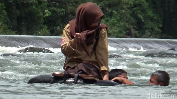 Siswa membantu siswi menyeberangi sungai menggunakan ban