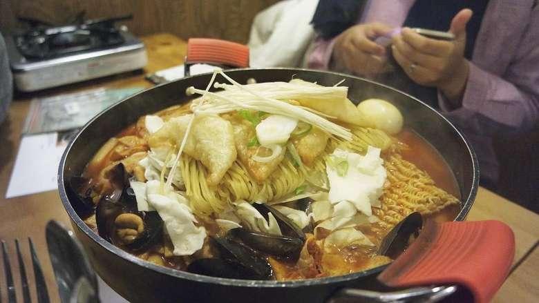 Ini menu makanan hangat yang nikmat khas Korea yang disukai Dea. Kuahnya yang agak kemerahan makin enak disantap dengan mie, jamur dan beberapa pelengkap seperti telur dan seafood. Slurp, enak!Foto: Instagram @deaannisa
