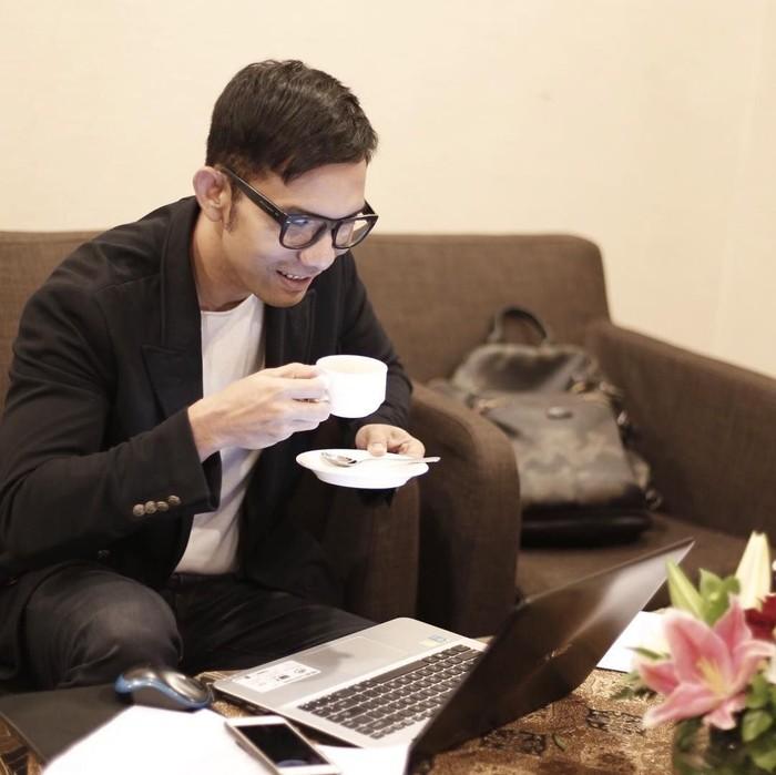 Lewat instagram pribadinya @indraherlambang, ia sering membagikan foto bersama makanan. Kali ini ia asyik berpose memegang secangkir kopi di depan laptopnya. Foto: instagram @indraherlambang