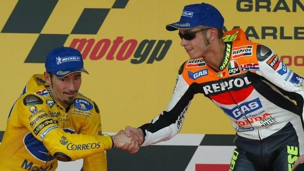 Moto GP World Champion and winner of the Moto Grand Prix of Spain, Italian Valentino Rossi (R) shakes hands with his fellow compatriot and second placed Max Biaggi on the podium 11 May 2003, in Jerez. Australian Troy Bayliss finished third. AFP PHOTO/ Pierre-Philippe MARCOU / AFP PHOTO / PIERRE-PHILIPPE MARCOU
