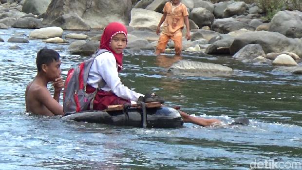 Siswi menyeberangi sungai dengan menaiki ban