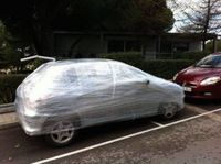 Parkir sembarangan, mobil ini dibungkus plastik.