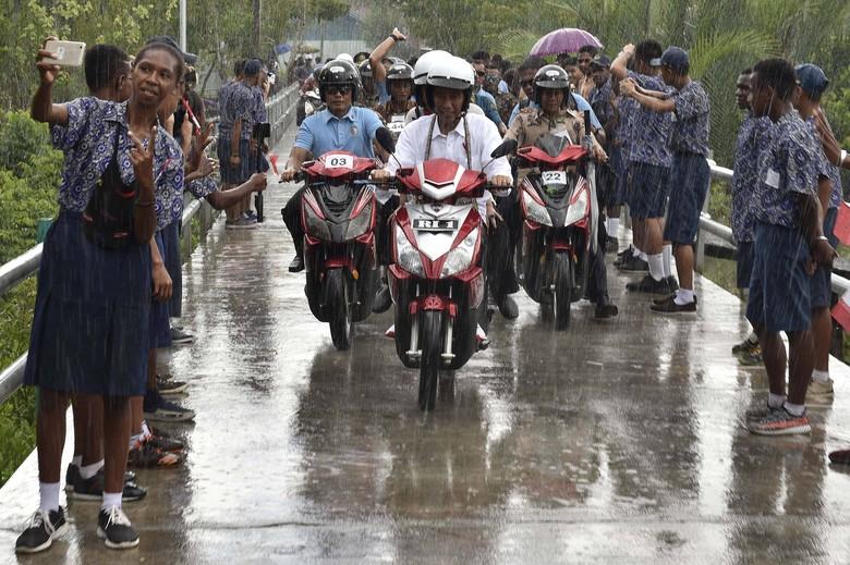 Presiden Joko Widodo hujan-hujanan naik motor listrik di Asmat. Foto: ANTARA FOTO/Puspa Perwitasari