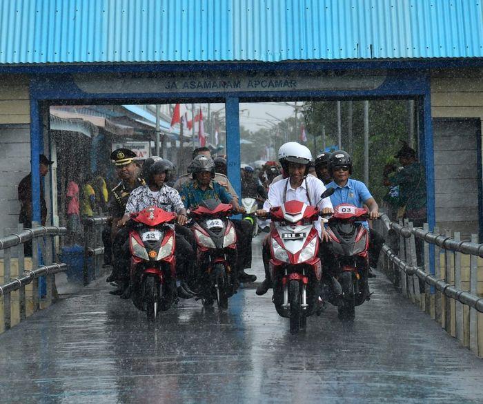 Jokowi menunggangi motor listrik bersama dengan Ibu negara Iriana Jokowi saat menuju Aula Wiyata Mandala, Dinas Pendidikan Kabupaten Asmat. Dok. Biro Pers Setpres.