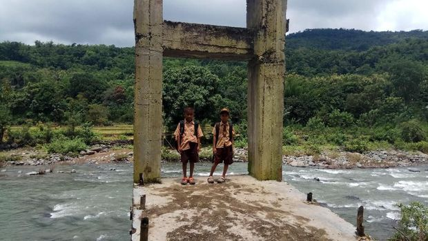 Karena tak ada jembatan, para siswa mesti menyeberangi derasnya arus sungai