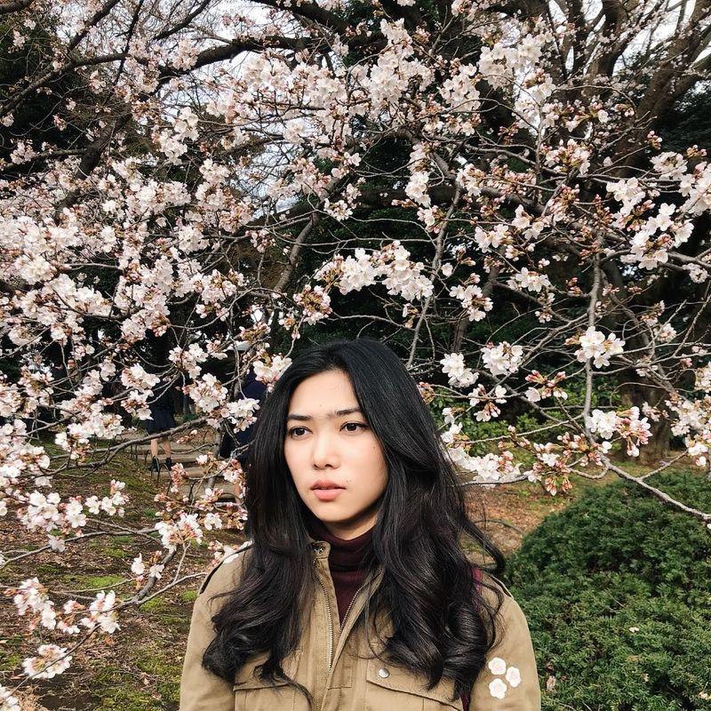 Isyana Sarasvati berpose dengan latar sakura yang bermekaran di Jepang bulan Maret kemarin. Setelah Jepang, di bulan April ini pun ia juga traveling ke Korea Selatan (isyanasarasvati/Instagram)