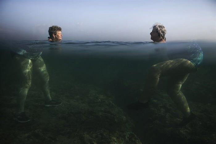 Terlihat dua wanita tua sedang berenang di tengah laut. Namun, karena pembiasan air asin jadinya menghasilkan efek yang mengesankan, seolah kepala dua wanita tersebut terlepas dari tubuhnya. Foto: Twitter @LondonImageFest