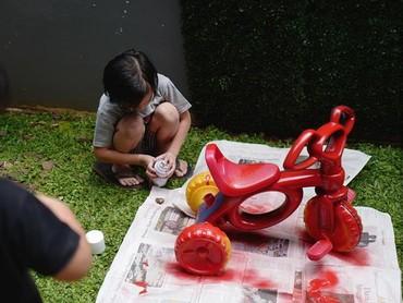 Ini Saga sedang mengecat sepeda lamanya. Warnanya merah. Apakah si kecil juga suka mengecat seperti Saga, Bun? Kalau lihat begini, lucu ya, he-he. (Foto: Instagram @sagaomarnagata)
