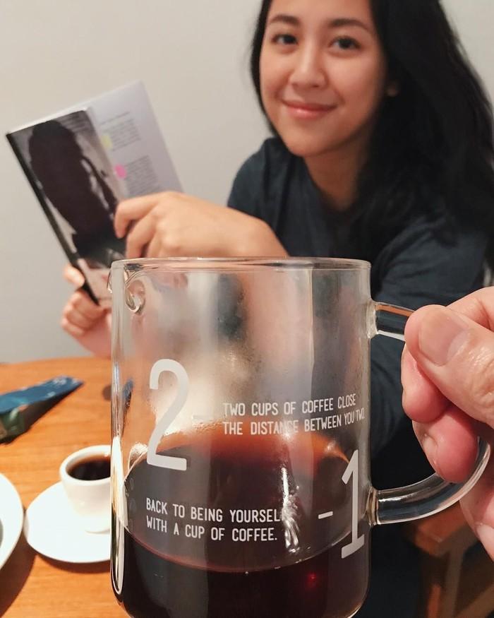 Senyum manis Sherina terlihat jelas dibalik gelas kaca berisi kopi. Hayoo siapa yang memegang gelasnya? Foto: Instagram @sherinasinna