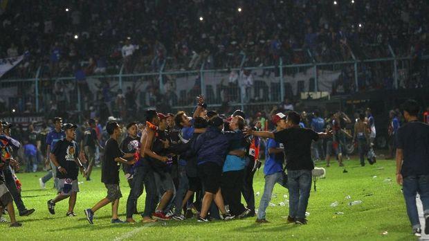 Suporter memasuki lapangan saat terjadi kericuhan pada pertandingan antara Arema FC melawan Persib Bandung dalam Liga I di Stadion Kanjuruhan. (