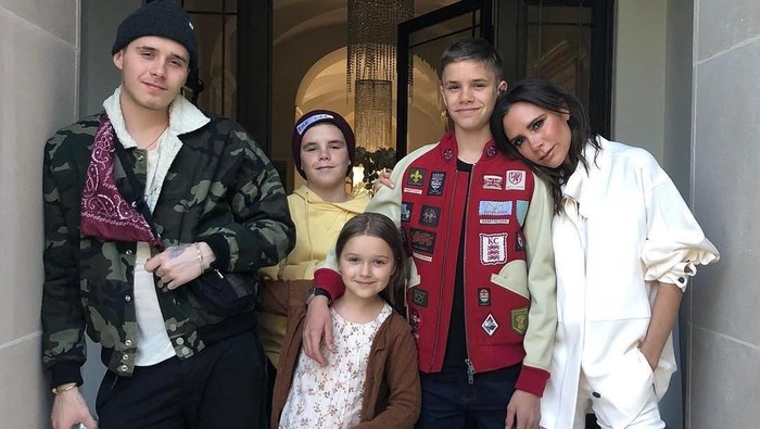 NEW YORK, NY - FEBRUARY 11: Designer Victoria Beckham embraces Romeo Beckham seated next to Harper Beckham, Cruz Beckham and David Beckham at the Victoria Beckham - fashion show February 2018 during New York Fashion Week on February 11, 2018 in New York City.  (Photo by JP Yim/Getty Images)