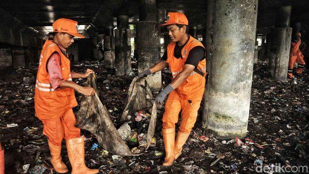 Pasukan oranye mengangkut sampah secara manual
