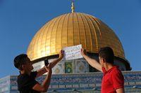 Foto tulisan tangan berlatar Dome of the Rock (Ammar Awad/Reuters)