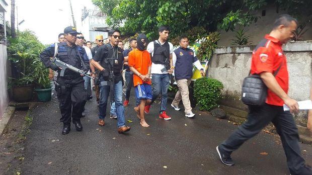 Tersangka dibawa ke TKP dengan tangan terborgol dan dikawal ketat polisi bersenjata api