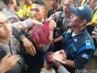 Seorang pemuda berambut merah dibawa petugas keamanan.