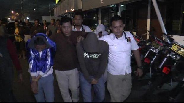 Dua dari 7 terduga pelaku (berjakket biru dan abu-abu) dibawa polisi