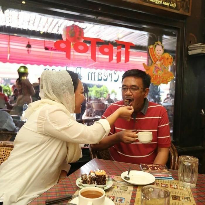So sweet! Saat berada di salah saru kedai kopi wilayah Medan, Happy Farida dengan lembut menyuapi sang suami kue cokelat. Djarot terlihat menikmati kue cokelatnya dengan secangkir kopi. Foto: Instagram @happydjarot
