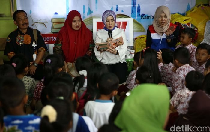 Plt Direktur Utama Pertamina Nicke Widyawati (tengah) membacakan dongeng untuk anak-anak di Rumah Baca Banyu Ilmi, Kampung Baru, Balikpapan, Kalimantan Timur, Kamis (26/4/2018).
