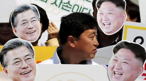 Warga membawa topeng Presiden Korsel Moon Jae-in dan pemimpin Korut Kim Jong-il.