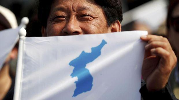 Warga membawa bendera unifikasi Korea, April 2018.