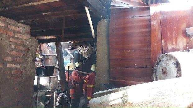 Petugas menyisir titik api di dalam bangunan kontrakan