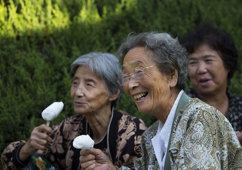 Adalah Eric Lafforgue seorang fotografer yang sudah berkeliling Korea Utara sampai 6 kali.Foto warga korea sedang makan es krim di taman Nasioanl Pyongyang, Korea Utara. (Foto: Eric Lafforgue)