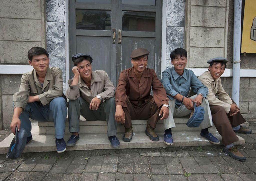 Para aktor duduk di tangga sambil tertawa di Studio film Pyongyang, Korea Utara. Ia mengisahkan bagaimana pemerintah mengendalikan para wisatawan asing untuk mengikuti semua kebijakan ketat yang telah ditetapkan mulai dari tempat wisata hingga foto-foto yang boleh diambil. (Foto: Eric Lafforgue)