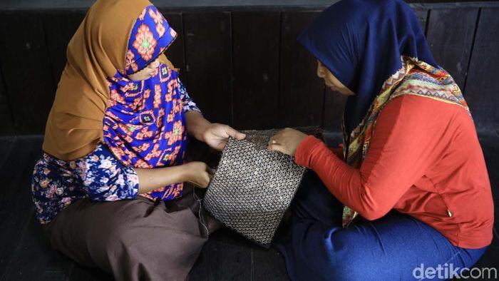 Pengrajin yang merupakan ibu rumah tangga membuat kerajinan berupa tas anyaman yang bahannya dari limbah kayu dan batok kelapa.
