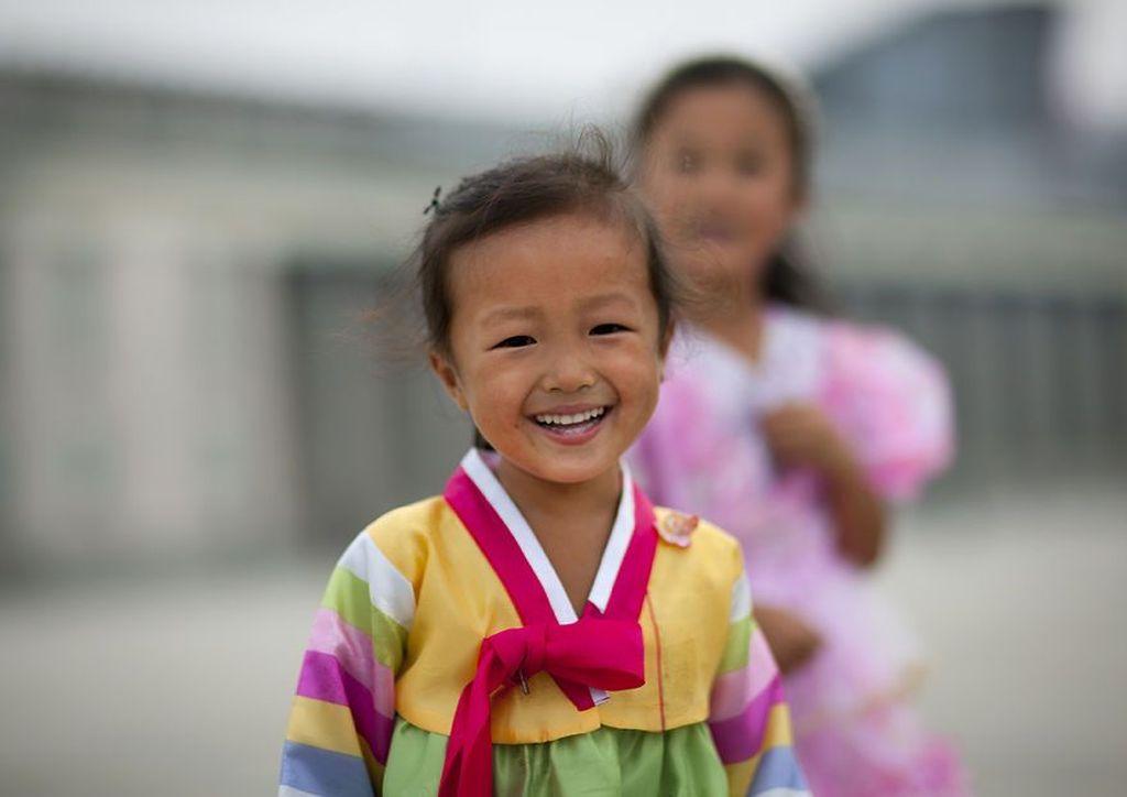 Lewat fotografinya ia menggemparkan dunia dengan hasil jepretan yang jarang diketahui publik dengan membuka kehidupan terlarang di Korea Utara. Senyum si mungil mengenakakn pakaian tradisional. (Foto: Eric Lafforgue)