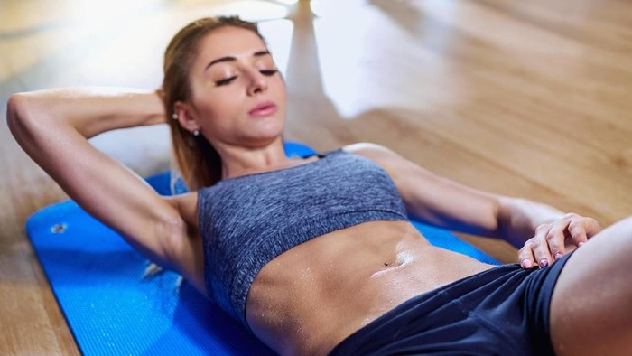 Side view image of fitness woman doing sit ups on an exercise mat. Muscular young woman lying on exercise mat with her hands behind head doing stomach exercises.