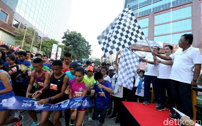 Ketua INASGOC Erick Thohir (tengah) melepas peserta lari BRI Sunday Fest 2018.
