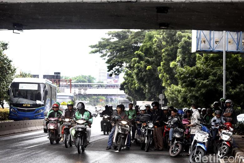 Hujan, Pemotor Berteduh di Kolong Jembatan. Foto: Rengga Sancaya