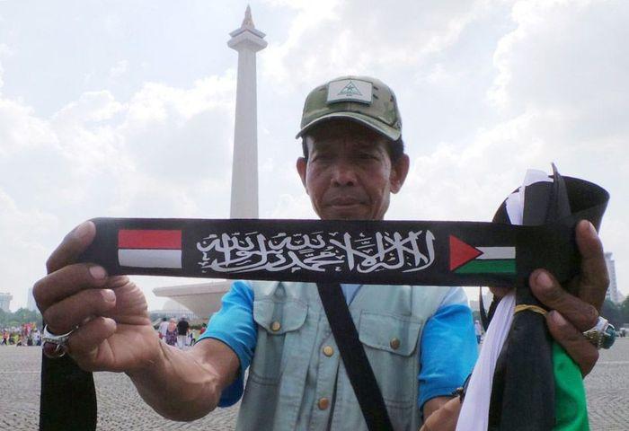 Seorang pedagang asal Bandung, Jawa Barat bernama Ade adalah salah satunya. Pria ini menjual pita bernuansa aksi yang biasa dipakai sebagai ikat kepala para peserta aksi.