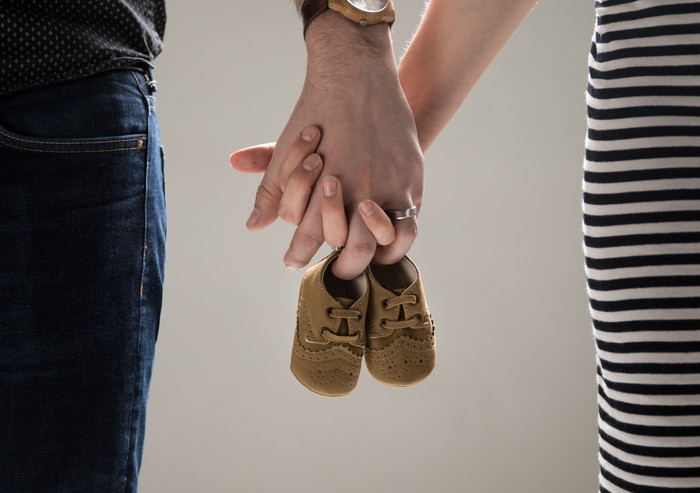 A couple of adults holding a pair of baby shoes.