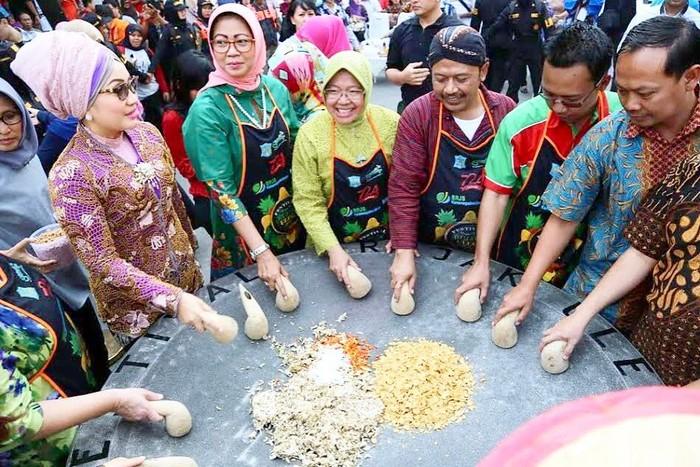 Wah, Wali Kota perempuan pertama di Surabaya itu ngulek bumbu rujak bareng di Festival Rujak Uleg 2017. Dengan banyaknya cabe hingga kacang, dibutuhkan cobek khusus yang berukuran cukup besar. Foto: Instagram trirismaharini