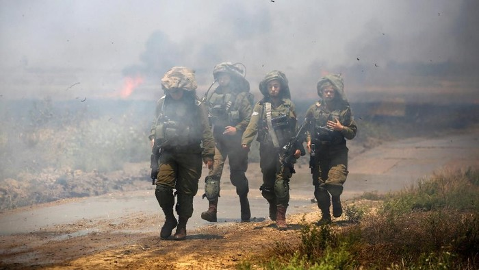 Israeli soldiers patrol near a burning field on the Israeli side of the border between Israel and Gaza, May 14, 2018. REUTERS/Amir Cohen     TPX IMAGES OF THE DAY