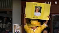 Ada seorang wanita yang memakai baju kuning menunjukkan tulisan Here In Spirit. Ia pun seorang penggemar Pangeran Harry dan Meghan Markle. Foto: Leon Neal/Getty Images