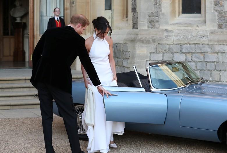 Pangeran Harry membukakan pintu Jaguar E-Type Concept Zero untuk sang istri Meghan Markle. Foto: Reuters